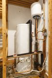 Hot water cylinder. Unvented hot water cylinder and expansion vessel in an airing cupboard. UK plumbing stock photo