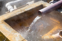 Hot water flowing out of pipe, hot spring water boiling Stock Photos
