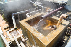 Hot water flowing out of pipe, hot spring water boiling Stock Photo