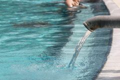 Hot water flowing into a pool, spa background. Hot thermal water flowing into a hotel pool from a metal tap, spa background stock photography