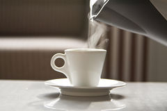 Hot water flowing from a teapot in a white cup Royalty Free Stock Images