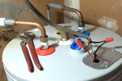 Hot Water Heater Installation. A completed hot water install showing final installation tips in wiring and connecting plumbing Royalty Free Stock Photography