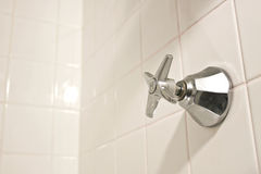 Hot Water Knob. A hot water faucet knob on a white tiled shower wall Royalty Free Stock Photography