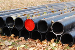 Hot water pipes. Bunch of black pipes prepared for construction laying in the fallen leaves Royalty Free Stock Images