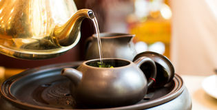 Hot water pouring into ceramic teapot stock photos