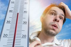 Hot weather concept. Young man is sweating. Thermometer is showing high temperature. Sun in background.  royalty free stock photos