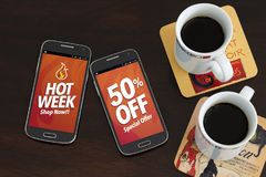 Hot Week 50% Off discounts. Advertising, Special Offer. Two cell phones and two coffee cup over the table. Marketing, Internet bus royalty free stock photography