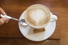 Hot white ceramic coffee cup with heart shape latte art on woode. N background Royalty Free Stock Images