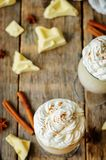 Hot white chocolate with whipped cream and cinnamon on a wood ba stock images