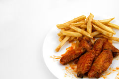 Hot Wings and Fries. A Plate of Hot Chicken Wings and French Fries royalty free stock photo
