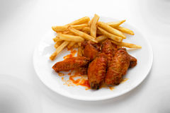 Hot Wings and Fries. A Plate of Hot Chicken Wings and French Fries royalty free stock photos