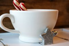 Hot winter beverage with peppermint sticks. Hot chocolate in a white mug with peppermint sticks and a glittery star ornament against a rustic wood background Stock Images