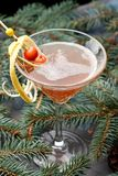 Hot Winter Cocktail in Martini Glass on Fir Branch. Alcohol Wine Christmas Drink with Lemon Peel and Berries. Warm Side Vertical View stock photography