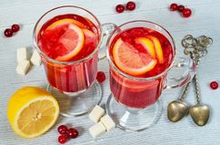 Hot winter healthy drink - cranberry tea or sangria with fresh lemon slices in glasses on the gray concrete kitchen background. Side view stock image