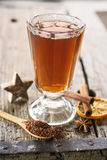 Hot winter spiced tea. In glass on wooden table Stock Image