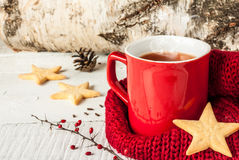 Hot winter tea in a red mug with christmas cookies. Hot winter tea in a red mug with star shaped christmas cookies and warm scarf - red and white rural still Royalty Free Stock Photography