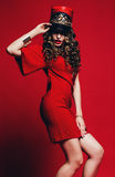 Hot woman with curly hair in red hat and dress Royalty Free Stock Photo