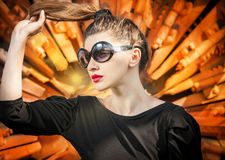 Hot woman in sunglasses with long hair in light and red textured background Stock Photography