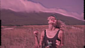 Sexy girl dancing on a road in the mountains on a sunny day with effect VHS and change color effect. Accelerated video. A hot woman in a swimsuit is dancing on stock footage