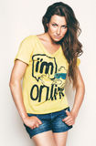 Hot woman in yellow t shirt and shorts. In studio Royalty Free Stock Photography