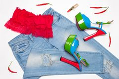 Hot women outfit of crop top, jeans, high heels with red chili p. Hot summer women outfit. Crop top, ripped skinny jeans, high heels, red lipstick with chili Royalty Free Stock Image