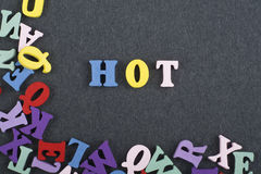 HOT word on black board background composed from colorful abc alphabet block wooden letters, copy space for ad text royalty free stock images