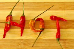 HOT word made from chilli on the wooden board Stock Photo