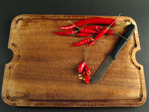 Hot work is done. Red peppers on wood with knife (chilli sliced Royalty Free Stock Image