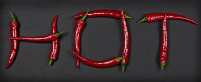 Hot written with chili peppers Royalty Free Stock Photo