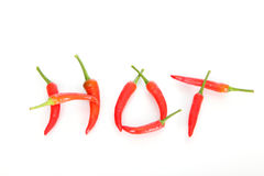 Hot written with red chili peppers Stock Images