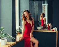 Hot young adult, proud and domineering woman dressed in a long scarlet red long dress, sexually demonstrates her naked. Graceful leg, crouching on the window royalty free stock photo