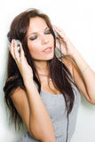 Hot young brunette enjoying music. Hot young brunette enjoying music, with her eyes closed in silver headphones Stock Images