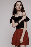Hot young brunette in red skirt and black blouse Stock Image