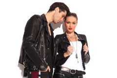 Hot young couple in leather clothes standing together. Sexy women pulling her jackets collar while her lover is standing close to her Stock Photo