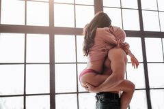 Hot young couple stand at window and hide heads under sweater. Woman sit on guy and embrace him with legs. Man hold her. Buttocks passiontly royalty free stock photos