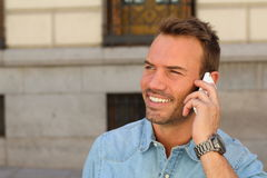 Hot young man calling with mobile phone . He is calling somebody by mobile telephone on the street Royalty Free Stock Photo