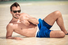 Hot young man lying on the beach Royalty Free Stock Photo