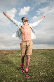 Hot young man walking with his hands in the air. Royalty Free Stock Photography
