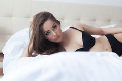 Hot young model posing at camera lying on bed Royalty Free Stock Images