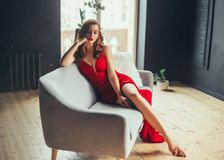 Hot young woman, dressed in a long scarlet red long dress, sexually shows her bare legs sitting on a grey sofa in a loft stock photo