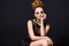 Hot young woman model with sexy lips makeup, strong eyebrows, clean shiny skin and bun hairstyle. Beautiful fashion. Hot young woman model with sexy dark red Royalty Free Stock Image