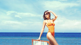 Hot, young woman with perfect legs posing on the beach nearby sun lounge. royalty free stock photography