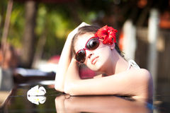 Hot young woman in sunglasses with flower in hair Stock Photo