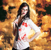 Hot zombie business woman on fire background. Dead sexy business woman standing in flames of desire in a depiction of the deadly sin LUST Stock Photos