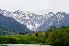 Hotaka mountain range and taisho ike pond in spring at kamikochi national park nagano. Japan Stock Images
