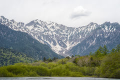 Hotaka mountain range and taisho ike pond in spring at kamikochi national park nagano. Japan Royalty Free Stock Photography