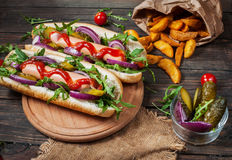 Hotdog aan boord met saus en frieten op een houten lijst Stock Afbeelding