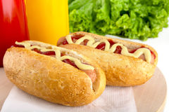 Hotdog with bottle of mustard and ketchup with salad on wooden d Royalty Free Stock Image
