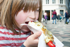 Hotdog child lunch fastfood denmark. Child eating hotdog with danish style red sausage on stroget in copenhagen. blond boy with fastfood lunch in sunshine Stock Photography