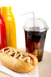 Hotdog with cola and bottle of mustard and ketchup on wooden desk Stock Photo